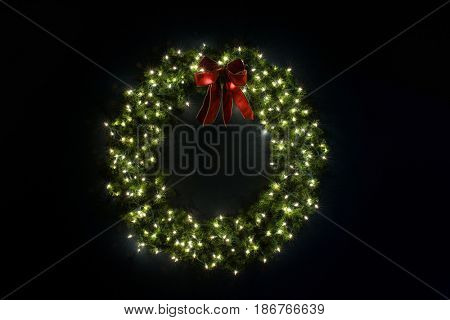 Lit Christmas Wreath on Navy Blue Wall