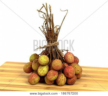 Lychee with leaves on a wooden board