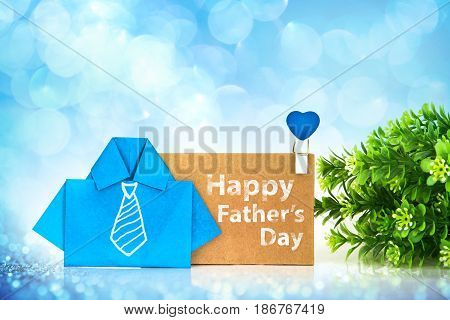 the blue origami shirt paper with white hand drawing necktie and Happy Father's day message on brown paper tag creative Father's day decoration with blue bokeh concept