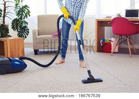 Cropped shot of pretty female cleaning with vacuum cleaner carpet
