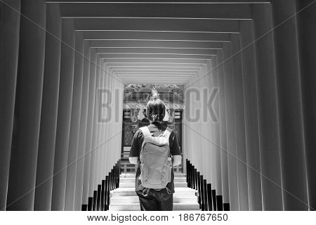 Black and white view Lady's backpacker in red archs at Ikuta shrine (God of love place) KobeJapan with selected focus.