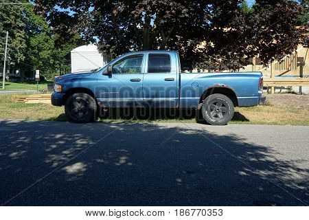 HARBOR SPRINGS, MICHIGAN / UNITED STATES - AUGUST 5, 2016: A Dodge Ram 1500 pickup truck is parked in the shade outside of a construction site in Harbor Springs.