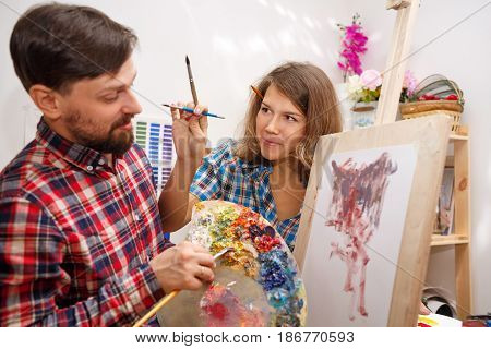 Students fool around in art school. The girl tries to decorate the face of her friend. Courses of drawing for adults.