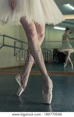 Ballerina in pointe shoes and tutu warming up before dance lessons. Crossed long slender female feet. Classical ballet. Prima ballerina.
