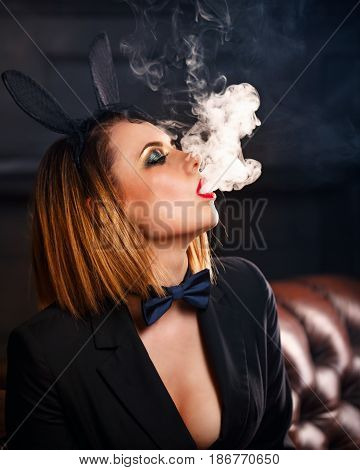 Young attractive girl in a jacket a butterfly tie and bunny ears smokes an e-cigarette. Femme fatale. Evening makeup smokey eye. She lets out a thick steam from her mouth. Pleasure in vice.