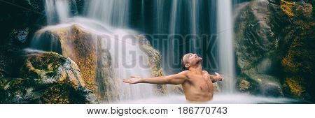 Man relaxing with freedom banner. Person with open arms in waterfall in tropical nature. Wellness spa concept in holiday nature. Wide landscape crop for panorama.