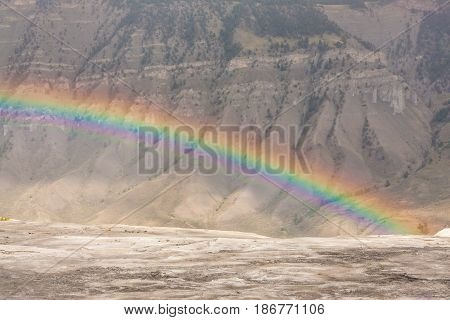 Landscape of a rainbow over the moon like terrain of the Mammoth Springs Wyoming USA.