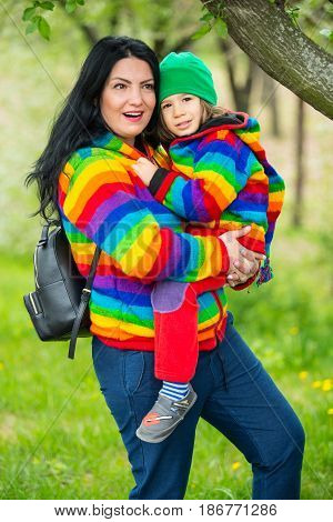 Amazed mother and son in park wearing rainbow hoodies