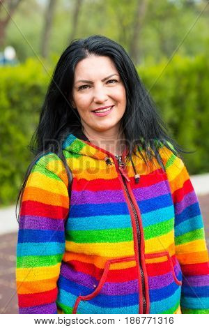 Happy woman in rainbow hoodie in park