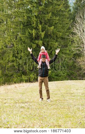 Cheerful dad and daughter having a walk in nature