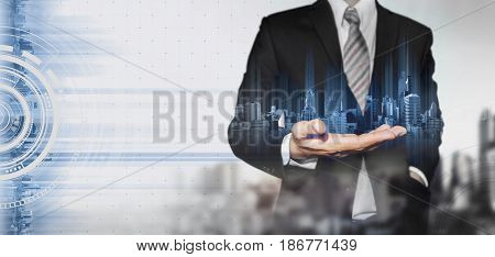 Businessman holding blue hologram of modern buildings, innovation technology concept