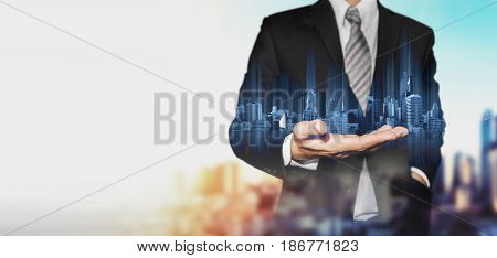 Businessman holding blue hologram of modern buildings, with blur background and copy space