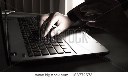 silhouette black and white of anonymous hacker typing on keyboard of laptop for remotely hacking and receiving personal information Payment Security Concept