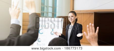 Young businesswoman making a presentation and asking for opinion in the meeting panoramic banner