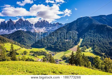 Lovely sunny autumn day. Odle mountain peaks and forested mountains surrounded by green Alpine meadows. Dolomites, Val de Funes valley