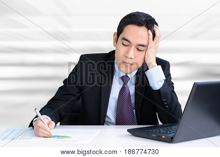 Stressed businessman working at the table with hand on his head