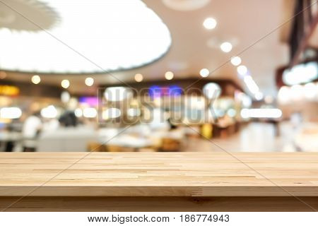 Wood table top on blur background of food court in shopping mall - can be used for montage or display your products