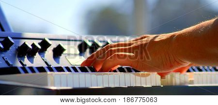 Latin jazz piano player performing solo in concert outside.