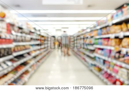 Blur image of aisle in supermarket with customers - for background