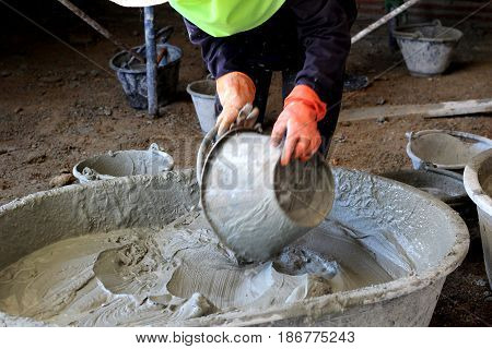 The image of a construction worker mixing cement.cement on April 20, 2017.