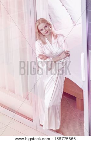 Portrait of beautiful young woman standing arms crossed at balcony doorway