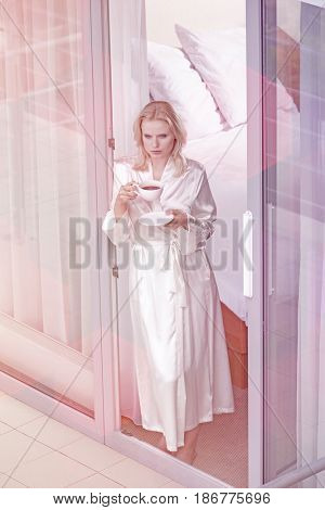 Beautiful young woman in robe having coffee at balcony doorway