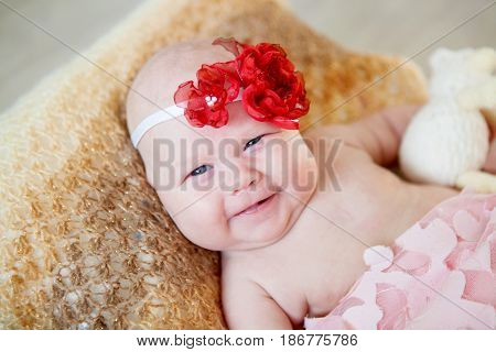 Beautiful little two month old girl with a red bow on her head smiling happily