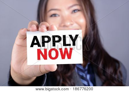 APPLY NOW message on the card shown by a woman