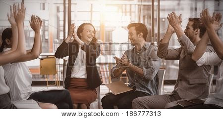Business executives applauding after presentation in office