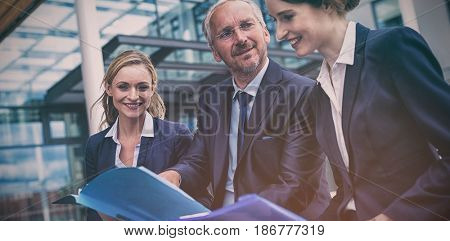 Businesspeople discussing over documents in office premises