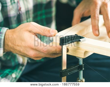 Man crafting wooden chair object keeping wooden boards in hands. Do it yourself project making process. Using press vise