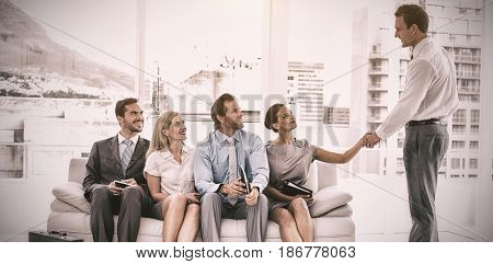 Businessman shaking hand with woman sitting with people waiting for interview in office