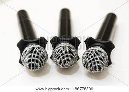 Selective focus on head microphones place on white table in blurred background.