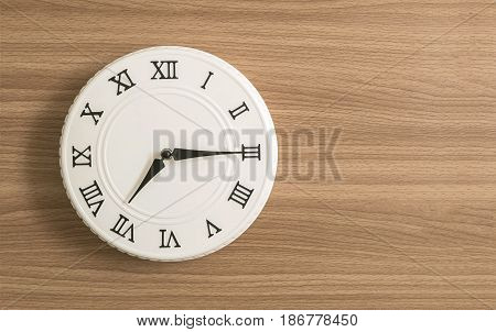 Closeup white clock for decorate show a quarter past seven o'clock or 7:15 a.m. on wood desk textured background with copy space