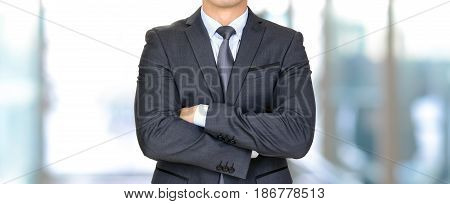 Anonymous businessman in dark gray suit crossing his arms - panoramic header business background
