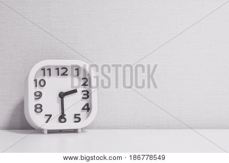 Closeup white clock for decorate show half past two o'clock or 2:30 p.m. on white wood desk and cream wallpaper textured background in black and white tone with copy space