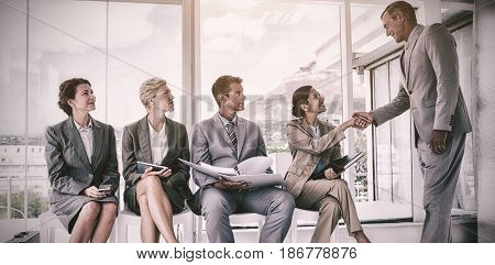 Manager welcoming people waiting for interview in office