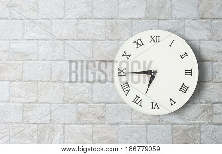 Closeup white clock for decorate show a quarter to seven or 6:45 a.m. on old brick wall textured background with copy space in interior concept