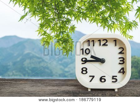 Closeup white clock for decorate show show a quarter to nine o'clock or 9:45 a.m. on blurred green leaves and mountain view background