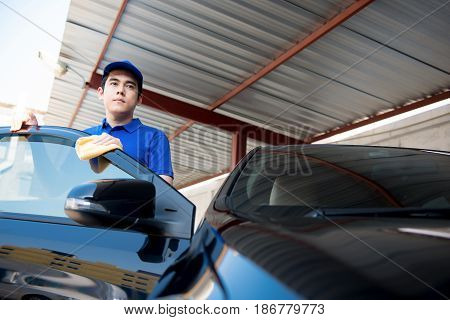 Auto cleaning staff standing at the car door