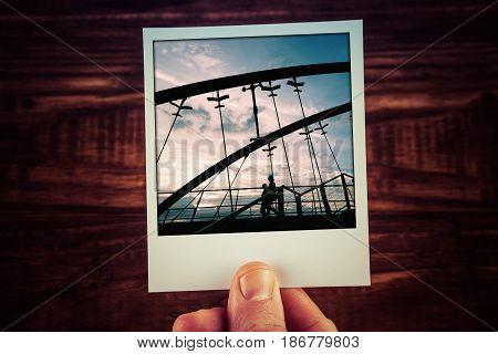 Hand Holding Polaroid Postcard Of Two People Silhouettes Walking On Frankston Bridge At Sunset. Trav