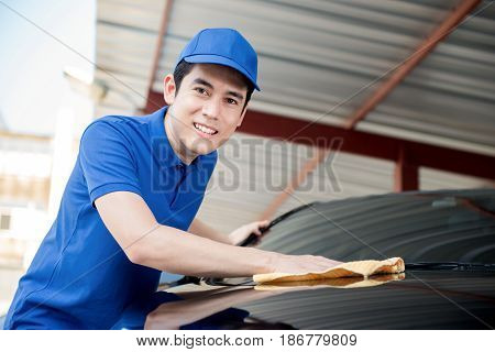 A man polishing (cleaning) car with microfiber cloth car detailing or valeting concept