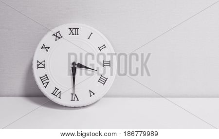 Closeup white clock for decorate show half past three o'clock or 3:30 p.m. on white wood desk and wallpaper textured background in black and white tone with copy space