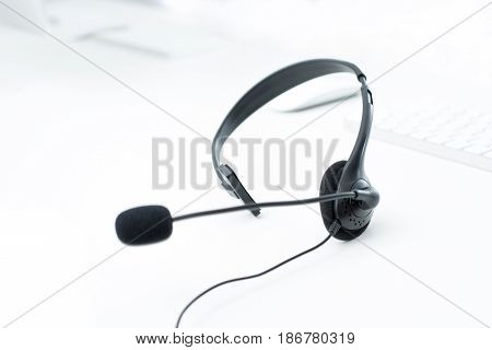 Microphone headset on white table with blur computer keyboard background - operator call centercustomer service and telemarketing concepts