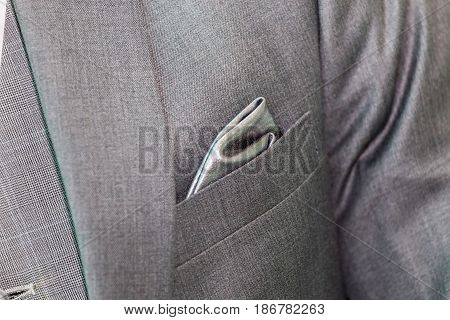 Close-up luxury gray handkerchief in the pocket of fashionable formal suit.
