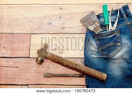 A hammer, a screwdriver, pliers and a spatula with blue ragged jeans lie on a wooden background