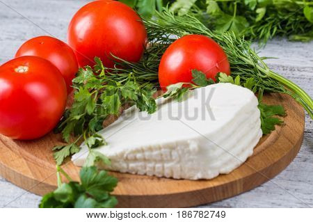 White Cheese, Knife, Parsley, Tomatoes On A Wooden Boards Background