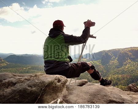 Tired Man Tourist  Sit With  Hurt Knee In Immobilizer Or Rock, Hold  Medicine Pole.  Open Forest Lan