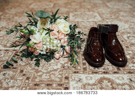 wedding bouquet on a background blue bow tie, leather shoes and wedding rings. Grooms wedding morning. Close up of modern man accessories