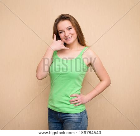Call me. Cheerful young women gesturing phone sign and smiling. Pretty girl shows a sign give me a call.